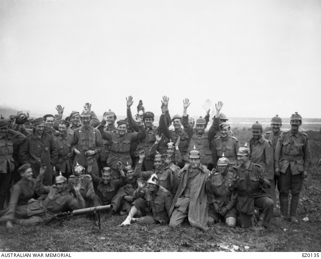 Informal group portrait of unidentified Australian soldiers sporting helmets (Pickelhauben) and caps captured from the Germans in the battle of Pozieres. Some have their hands raised, possibly in a feigned gesture of surrender. In the front on the ground is a Lewis gun. Australian War Memorial collection EZ0135
