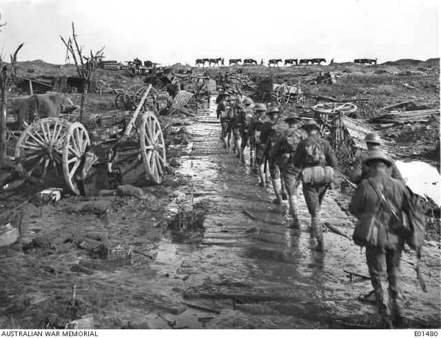 Idiot Corner, Ypres, 5 November 1917. Men and pack mules rounding Idiot Corner, on Westhoek Ridge, in Belgium, moving up to the front line. To follow the duckboard and corduroy track was to be seen silhouetted against the skyline, both from the Australian position and that of the enemy - before he was driven from Broodseinde Ridge. But passage over any part other than the top of the ridge was impossible owing to mud. At this point many transports and guns were wrecked by the constant shellfire, and others were lost in the morass. One vehicle actually sank out of sight in the ooze a little to the right of the picture. Australian War Memorial collection E01480