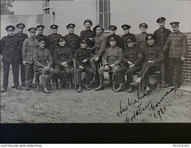 Cottbus, Germany. c. 1918. Formal group portrait of Australian prisoners of war (POW). The men are wearing a mixture of Australian Army uniform and a darker uniform and peaked hats issued by the Germans. They have been permitted to continue wearing their rank stripes, rising sun badges and awards. Australian War Memorial collection P02318.001