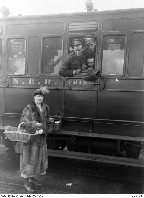 A lady worker of the Victorian League stands on the platform with two buckets, distributing fruit and cigarettes through an open window in the train carriage. The returned Australian prisoners of war entrained at Hull, for the receiving camp at Ripon, in England. Australian War Memorial collection D00175